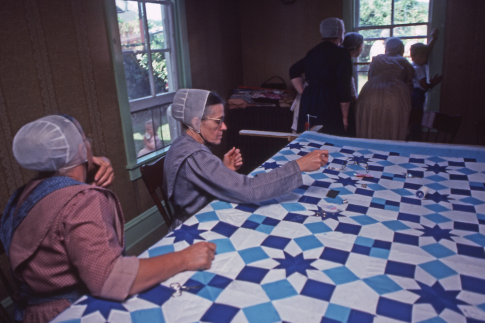 """Conservative """"Horse and Buggy"""" Mennonite women quilt while men erect a barn outside."""