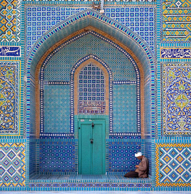 A man sits in a ornately tiled doorway at the Hazrat Ali Shrine in Mazar-i-Sharif, Afghanistan.