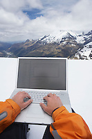 Man using laptop on snowy mountain peak close up of hands