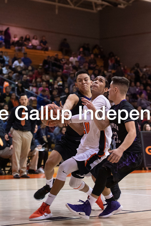 Quincy Smith (20) drives to the basket for Gallup and is fouled by Noah Nells (11) for Miyamura at the 75th Annual Gallup Boys Invitational Basketball Tournament, Saturday, Jan. 5, 2019 at Gallup High School.