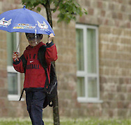 A child holds onto his umbrella on his way to Cleveland School in Dayton's Belmont neighborhood, Wednesday, June 4, 2008.