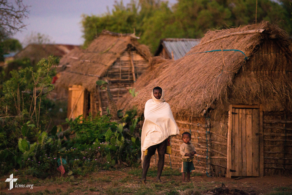 A man and a young boy stand outside a set of homes near Ambovombe, Madagascar, on Monday, Oct. 20, 2014. LCMS Communications/Erik M. Lunsford