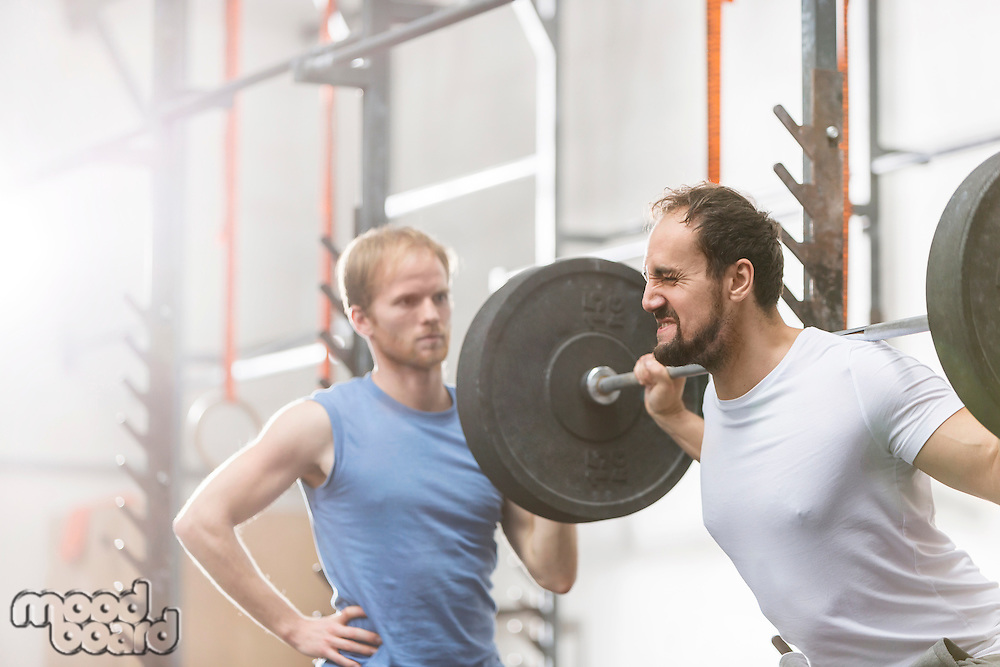 Man assisting friend in lifting barbell at crossfit gym