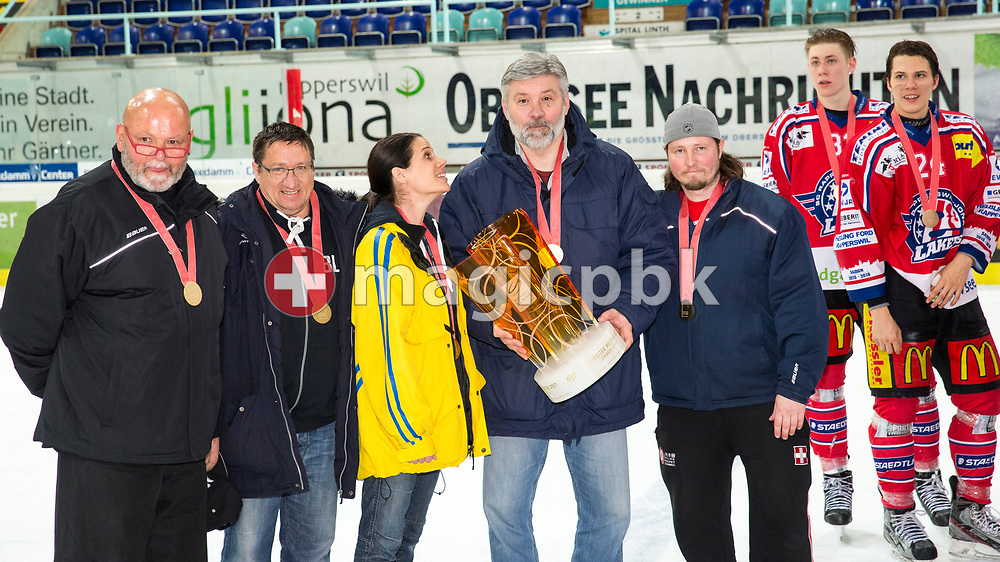 (L-R) Rapperswil-Jona Lakers staff members Ueli Blaser, Linus Beer, massage therapist Sina Riva, head coach Konstantin Kurashev and assistant coach Daniel Schneider pose for a photo with their gold medals and the Swiss Champion trophy while being watched by players Dario Turrin and Lars Mathis after winning the fifth Elite B Playoff Final ice hockey game between Rapperswil-Jona Lakers and ZSC Lions held at the SGKB Arena in Rapperswil, Switzerland, Sunday, Mar. 19, 2017. (Photo by Patrick B. Kraemer / MAGICPBK)