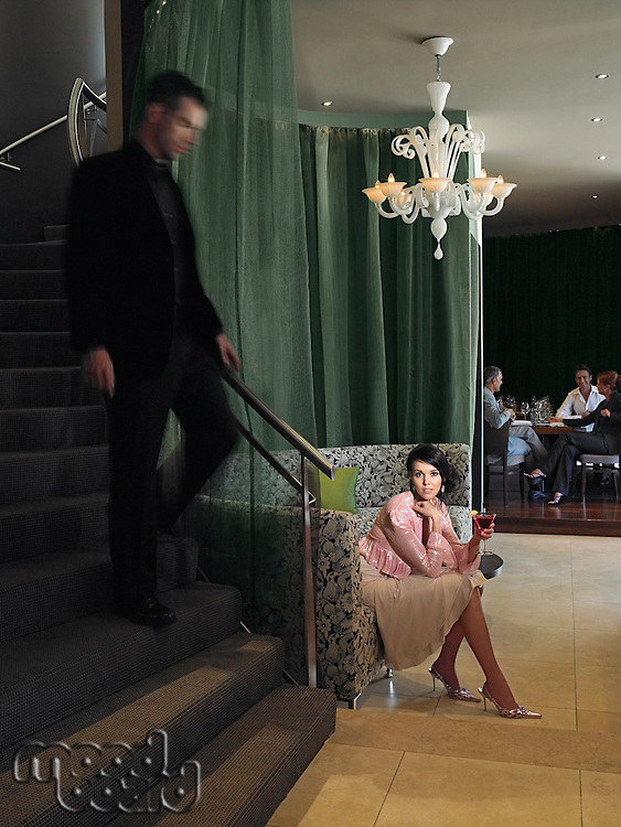 Woman waiting in hotel lobby for man descending staircase