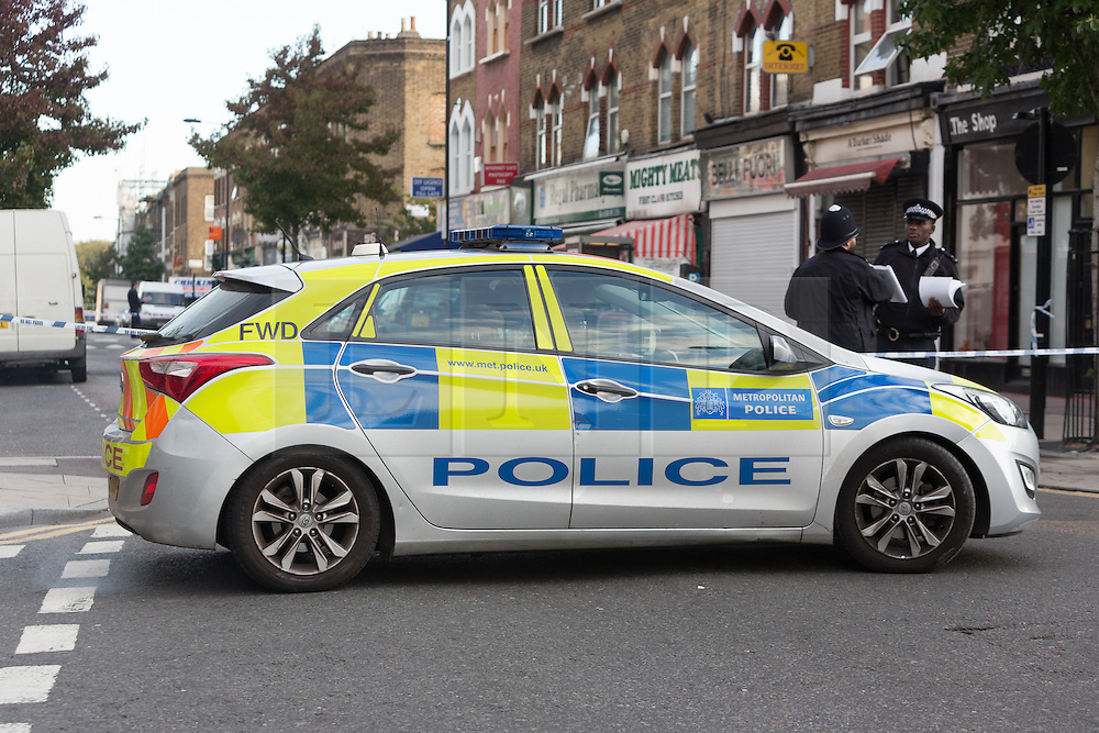 © Licensed to London News Pictures. 27/09/2015. London, UK. Police officers and a police car at the cordon on Chatsworth Road next to Regal Pharmacy. Police have launched a murder investigation after a man was shot dead in the street outside Regal Pharmacy next to Mighty Meats butcher shop in Chatsworth Road, Hackney, east London yesterday. Photo credit : Vickie Flores/LNP
