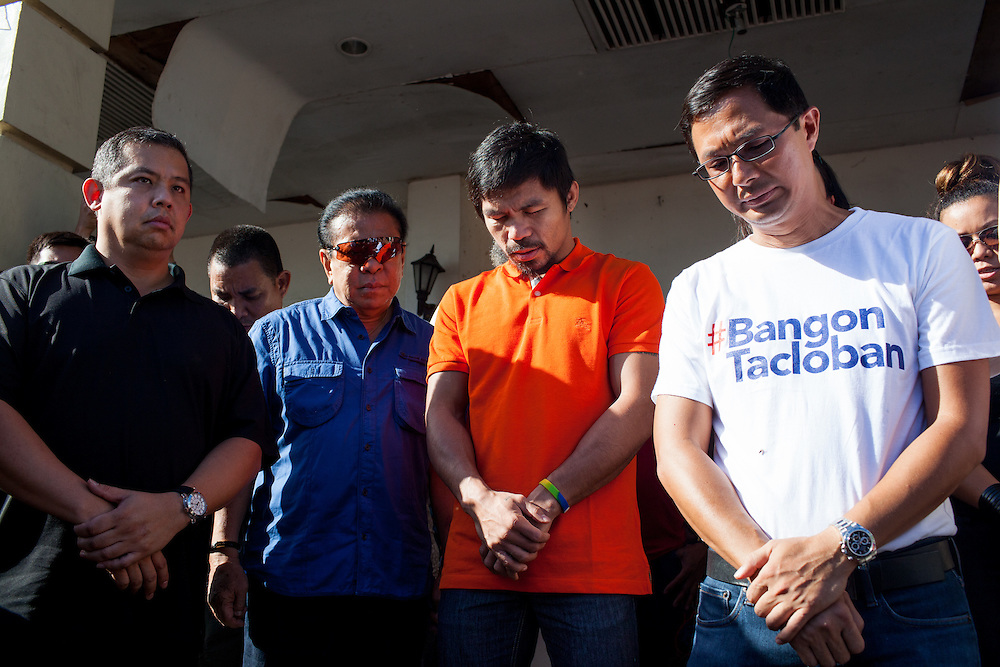 Manny Pacquiao prays at Tacloban City Hall during his visit.  To his right wearing Bangon Tacloban t-shirt or Stand Up Tacloban is Jimmy Sambo Yaokasin, Vice Mayor of Tacloban City.<br /> <br /> Manny Pacquaio visits victims of Typhoon Yolanda in Tacloban City.  Leyte, Philippines  December 2, 2013