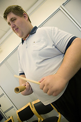 A day Service users with learning disabilities using a percussion instrument,