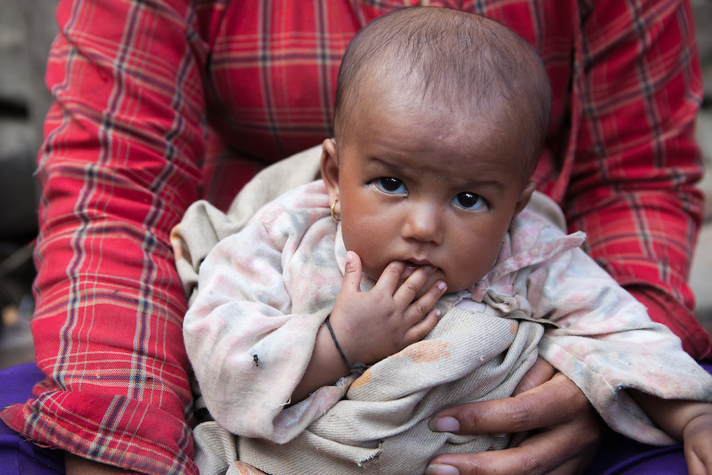Baby in de armen van haar moeder, in de grotendeels verwoeste stad Sakhu, nabij Kathmandu.