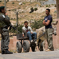 """Palestinian youths are stoped for a control by an Israeli border guards in the centre of the West Bank city of Hebron on May 18, 2009 during a visit by a delegation of ultra-nationalist Israeli MPs protesting against Israeli Prime Minister Benjamin Netanyahu's promotion of the easing of restrictions on Palestinians. Netanyahu will have first face to face meeting with President Barack Obama amid divisions over Middle East peacemaking and Iran's nuclear ambitions. The hawkish premier, who wants a """"fresh"""" approach to the Israeli-Palestinian conflict, will unveil in the White House meeting on May 18 his long-awaited policy for regional peace focused on countering Iran, aides said. Photo by Olivier Fitoussi"""
