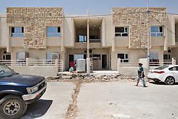 © Licensed to London News Pictures. Hamdaniyah, Iraq. 26/07/2014.  A row of partially built houses, home to Christian refugees from Mosul, are seen in the Christian town of Hamdaniyah, Iraq.<br /> <br /> <br /> Having taken over Mosul Iraq's second largest city in June 2014, fighter of the Islamic State (formerly known as ISIS) have systematically expelled the cities Christian population. Despite having been present in the city for more than 1600 years, Christians in the city were given just days to either convert to Islam, pay a tax for being Christian or leave; many of those that left were also robbed at gunpoint as they passed through Islamic State checkpoints.. Photo credit : Matt Cetti-Roberts/LNP