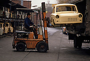A new Trabant car shell is lifted by forklift from a truck at the East German auto maker VEB Sachsenring Automobilwerke Zwickau in Zwickau, Saxony.  A worker carefully manoeuvres the unfinished bodywork into a crate where other vehicles await completion on the production line. The Trabant was the most common vehicle in East Germany - Like the Beetle in the West, its Peoples' Car with a 595 cc, two-cylinder air-cooled engine. It had space for four, was compact, light and durable with its distinctive body shape constructed from Duroplast panels attached to a galvanized steel shell. It was in production without any significant changes for about 34 years, becoming a symbol for the cheap, cheerful and polluting possessions for Communist Europeans. When the Berlin Wall eventually fell, Trabants coughed and spluttered onto West German roads for the first time.