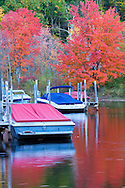 Docked pleasure boats on a river in New Hampshire in Autumn.