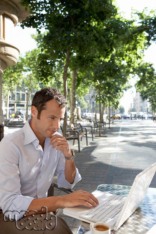 Businessman using laptop at outdoor cafe
