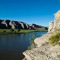 a man looks over the missouri river breaks national monument from high atop a rock outcropping, umrbnm, near judith landing on the wild and senic missouri river