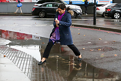 © Licensed to London News Pictures. 17/10/2019. London, UK. A woman leaps over a flooded area at a crossing on Tottenham High Road after heavy downpour in north London this afternoon. Photo credit: Dinendra Haria/LNP