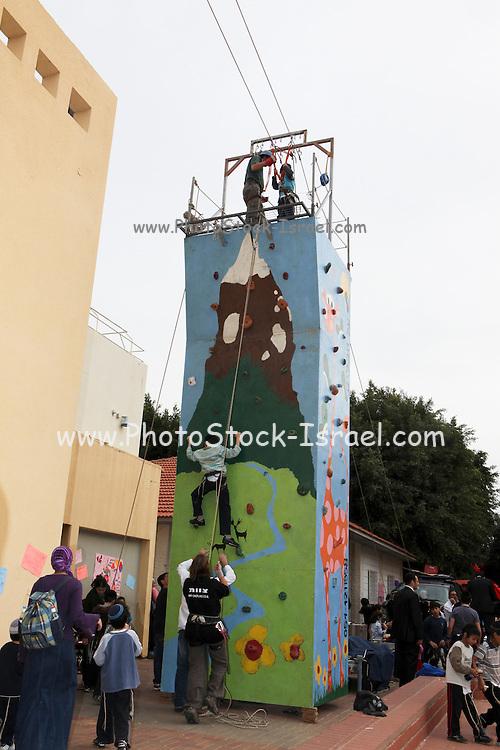 Child climbs a portable climbing wall