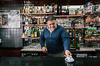 TARANTO, ITALY - 22 FEBRUARY 2018: Ignazio D'Andria, owner of the Mini Bar, serves a coffee in his bar in Tamburi, the working-class district adjacent the ILVA steel mill in Taranto, Italy, on February 22nd 2018.<br /> <br /> Taranto, a  formerly lovely town on the Ionian Sea has for the last several decades been dominated by the ILVA steel mill, the largest steel plant in Europe. It was built by the government in the 1960s as a means of delivering jobs to the economically depressed south, but has been implicated for a cancer as dioxin and mercury have seeped into local groundwater, tainting the food supply, while poisoning the bay and its once-lucrative mussels.