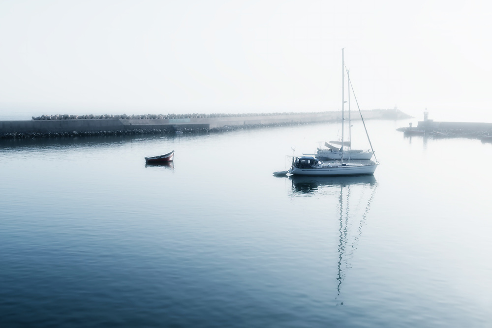 Two sailing boats (yachts) and a small motor boat anchored early morning. High key image with soft focus and glow.