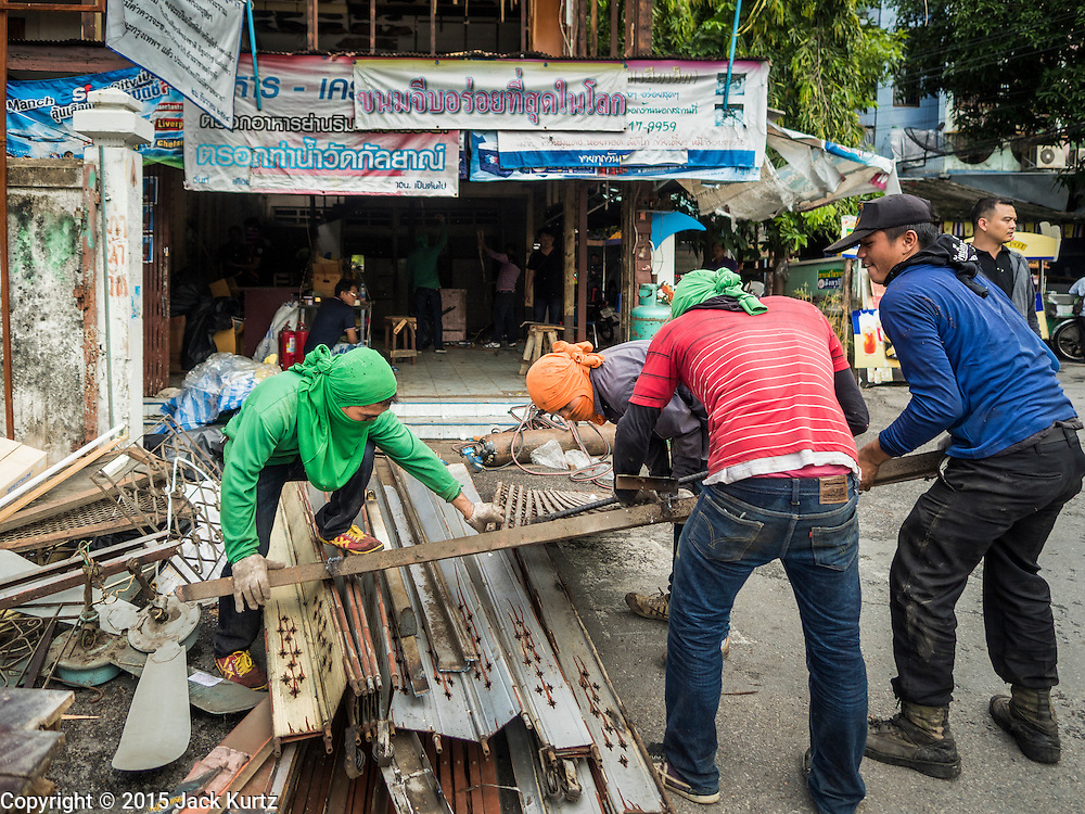10 SEPTEMBER 2015 - BANGKOK, THAILAND:  Demolition workers dismantle Chaiyasit Kittiwanitchapant's home in front of Wat Kalayanamit. Authorities started to destroy 54 homes in front of Wat Kalayanamit, a historic Buddhist temple on the Chao Phraya River in the Thonburi section of Bangkok. Government officials, protected by police, seized the house of Chaiyasit Kittiwanitchapant, a Kanlayanamit community leader, who has led protests against the temple's abbot for trying to evict community members whose houses are located around the temple. Work crews went into Chaiyasit's home and took it apart piece by piece. The abbot of the temple said he was evicting the residents, who have lived on the temple grounds for generations, because their homes are unsafe and because he wants to improve the temple grounds. The evictions are a part of a Bangkok trend, especially along the Chao Phraya River and BTS light rail lines, of low income people being evicted from their long time homes to make way for urban renewal.     PHOTO BY JACK KURTZ