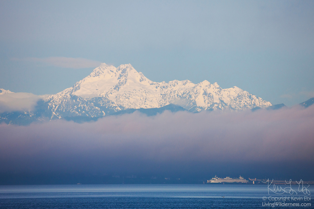 A Washington state ferry is docked at Kingston, Whidbey Island, as the Brothers, part of the Olympic Mountains, stand above a low layer of fog in this view across Puget Sound from the Edmonds waterfront.