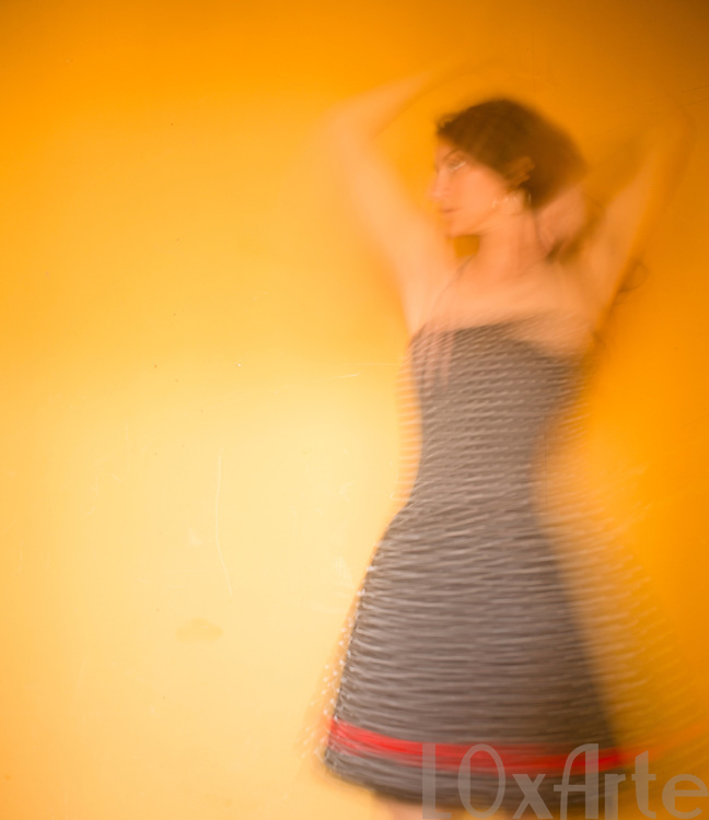 Carefree young woman in black dress with white spots and red accent dancing in front of a hot yellow background.