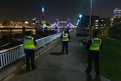 © Licensed to London News Pictures. 26/03/2020. London, UK. Local council enforcement officers stop to pay respects as Tower bridge and the London Shard are illuminated in blue this evening in recognition and appreciation of National Health Service (NHS) staff working in hospitals across the country during the ongoing COVID-19 coronavirus epidemic. Photo credit: Vickie Flores/LNP