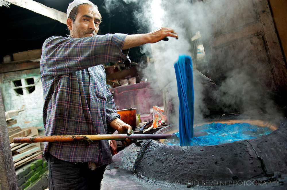Fabric dyer boils kashmir and pashmina wool in the colourful liquid used to dye textiles. Srinagar. Kashmir. India