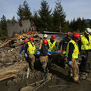 Rescuers remove a body as they search the massive debris pile after a mudslide destroyed dozens of homes and structures in the community of Oso, Wash. along the North Fork of the Stilliguamish River. Photographed on Monday, March 24, 2014 near Oso, Wash. (Joshua Trujillo, seattlepi.com)