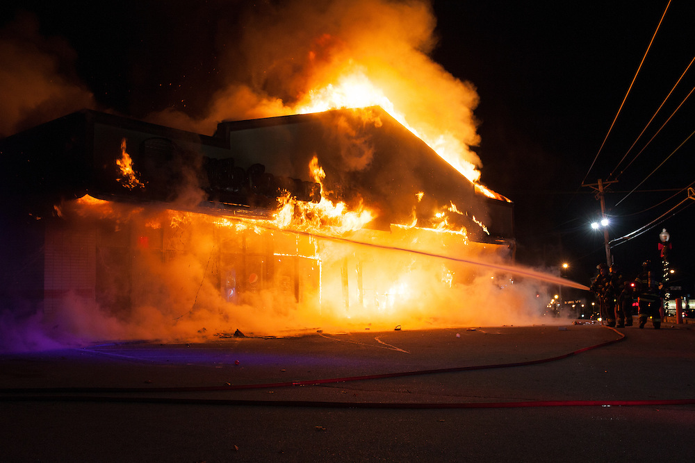 Firefighters work to extinguish a blaze set by rioters at a Little Caesar's restaurant in Ferguson. Dozens of cars and businesses have been set ablaze throughout the early evening. Demonstrations turned violent after the grand jury failed to indict Officer Darren Wilson for the shooting death of Michael Brown Jr.
