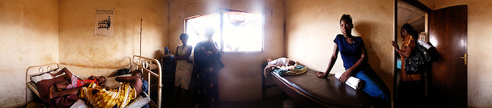 A women rest surrounded by friends and family after giving birth at the Kroo Bay clinic, Kroo Bay, Freetown, Sierra Leone.