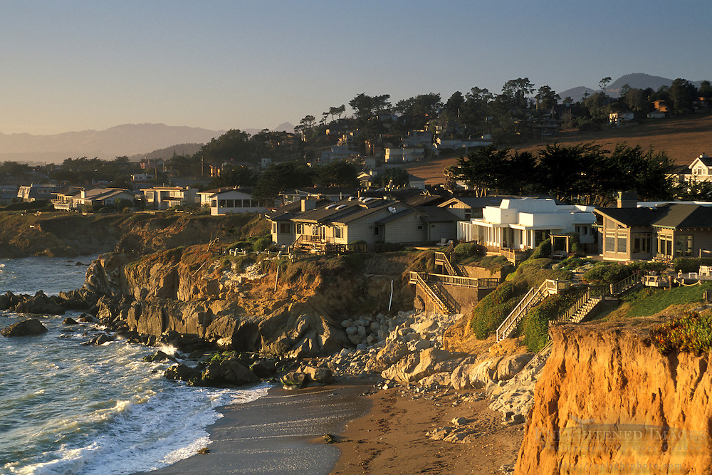 Homes atop coastal cliff bluffs over ocean beach in the small coastal town of Cambria, California