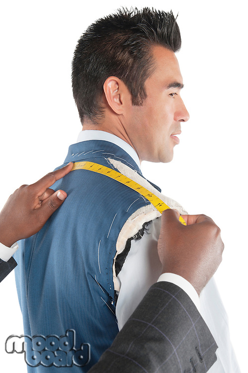 Profile view of man getting measured by tailor