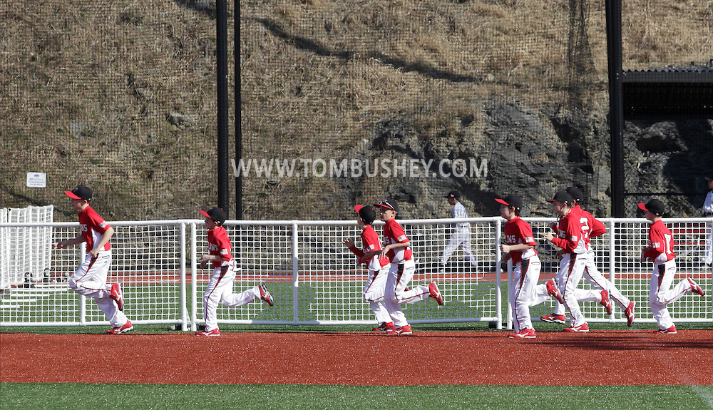 Chester, New York  - Players run across a field to warm up for their game in the TRUMP March Madness youth baseball tournament at The Rock Sports Park on March 17, 2012. ©Tom Bushey / The Image Works