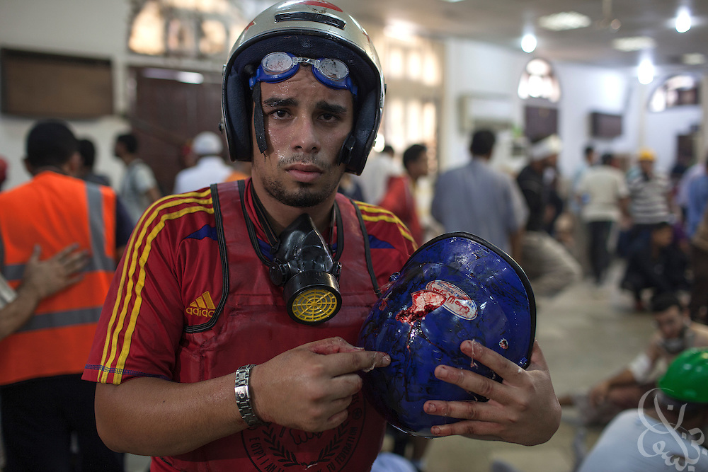 A pro-Morsi demonstrator holds the helmet of a protestor he says was shot dead earlier by police (a bullet hole and brain tissue was visible on the helmet) as he stands inside a packed field hospital inside the Rabaah al-Adawiya protest camp in Nasr City during the August 14, 2013 Ministry of Interior/Police operation to clear the protest by force. The assault, which began at 7am with police moving in to seal the surrounding streets included tear gas and live fire, and there are reports of large numbers of killed and wounded protesters.