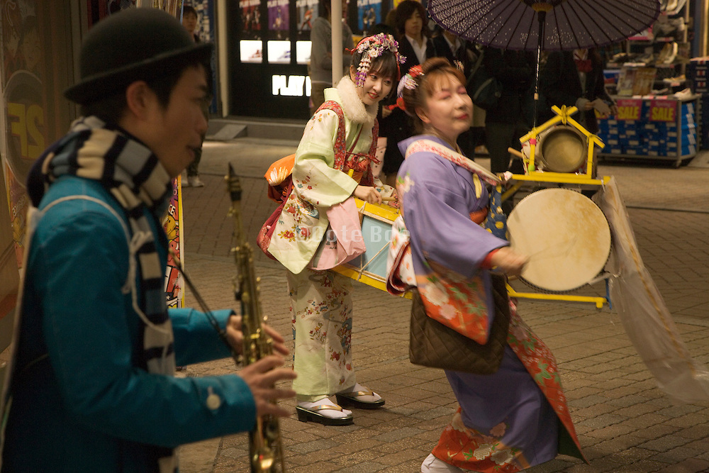 Japanese vaudeville band playing in front of a pachinko parlor Shibuya shopping street
