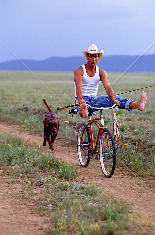 cowboy goofing around on a bicycle with fish, a fishing rod and a dog on a dirt road in New Mexico
