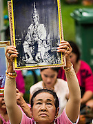 13 OCTOBER 2016 - BANGKOK, THAILAND:  A woman holds up a portrait of Bhumibol Adulyadej, the King of Thailand, while she prays for him at Siriraj Hospital. Thousands of people came to the hospital to pray for the beloved monarch. Bhumibol Adulyadej, the King of Thailand, died at Siriraj Hospital in Bangkok Thursday, October 13, 2016. Bhumibol Adulyadej, 5 December 1927 – 13 October 2016, was the ninth monarch of Thailand from the Chakri Dynasty and is known as Rama IX. He became King on June 9, 1946 and served as King of Thailand for 70 years, 126 days. He was, at the time of his death, the world's longest-serving head of state and the longest-reigning monarch in Thai history.      PHOTO BY JACK KURTZ