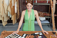 Portrait of beautiful female fashion designer standing at table with layouts