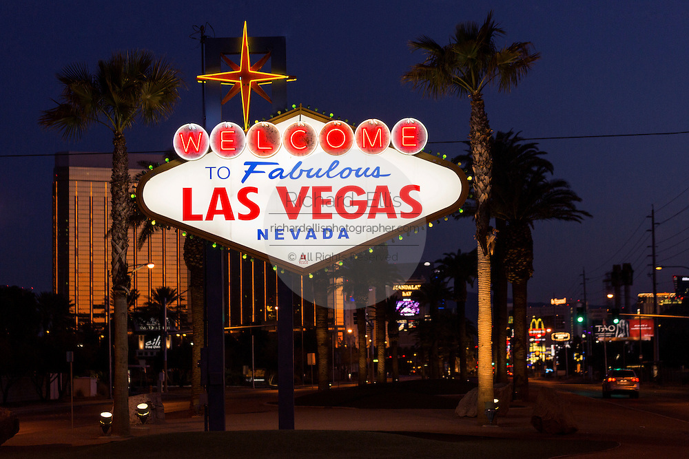 Famous neon Welcome to Fabulous Las Vegas sign surrounded by palm trees along the strip at twilight.