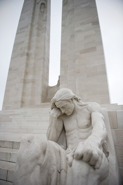 The Male mourner sculpture in front of the twin white pylons of the Canadian National Vimy Memorial dedicated to the memory of Canadian Expeditionary Force members killed in World War one. The monument is situated at a 100 hectare preserved battlefield with wartime tunnels, trenches, craters and unexploded munitions. The memorial designed by Walter Seymour Allward opened in 1936.
