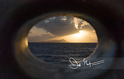 Porthole looking out over the Caribbean Sea and the island of Saint Lucia at sunrise.