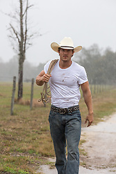 rugged All American cowboy walking on a dirt road in the rain