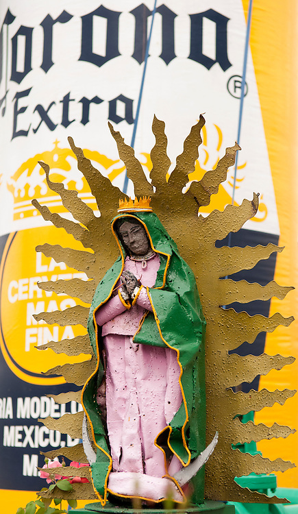 Religious sculpture in front of inflatable beer bottle at the Corona brewery in Guadalajara, Mexico.