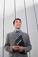 Young Businessman standing holding notebook low angle view