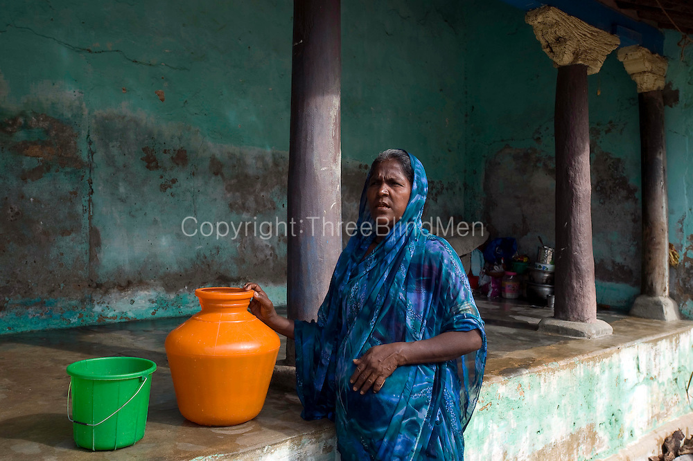 Woman with water pot standing in front of the 'thinnai' (raised platform) of the house. Home in Nagapattinam town. South India.