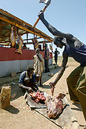 Butchers prepare meat at a stall in the Kapoeta Barak Market (New Market). The area of the market lies on land that was a defensive barrior mine field during the war.<br /> Kapoeta, South Sudan. 25/09/2009.