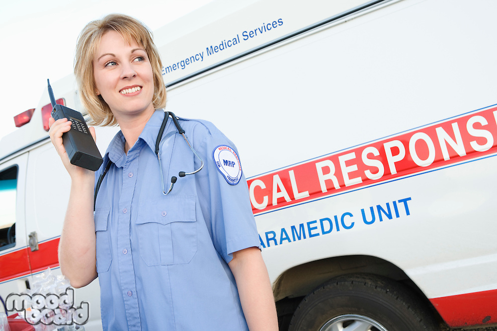 Paramedic using walkie talkie by ambulance