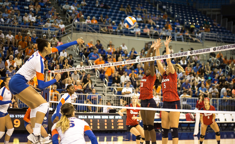 Florida's Alex Holston jumps to spike the ball and score against St. John's. (photo by Samuel Navarro)