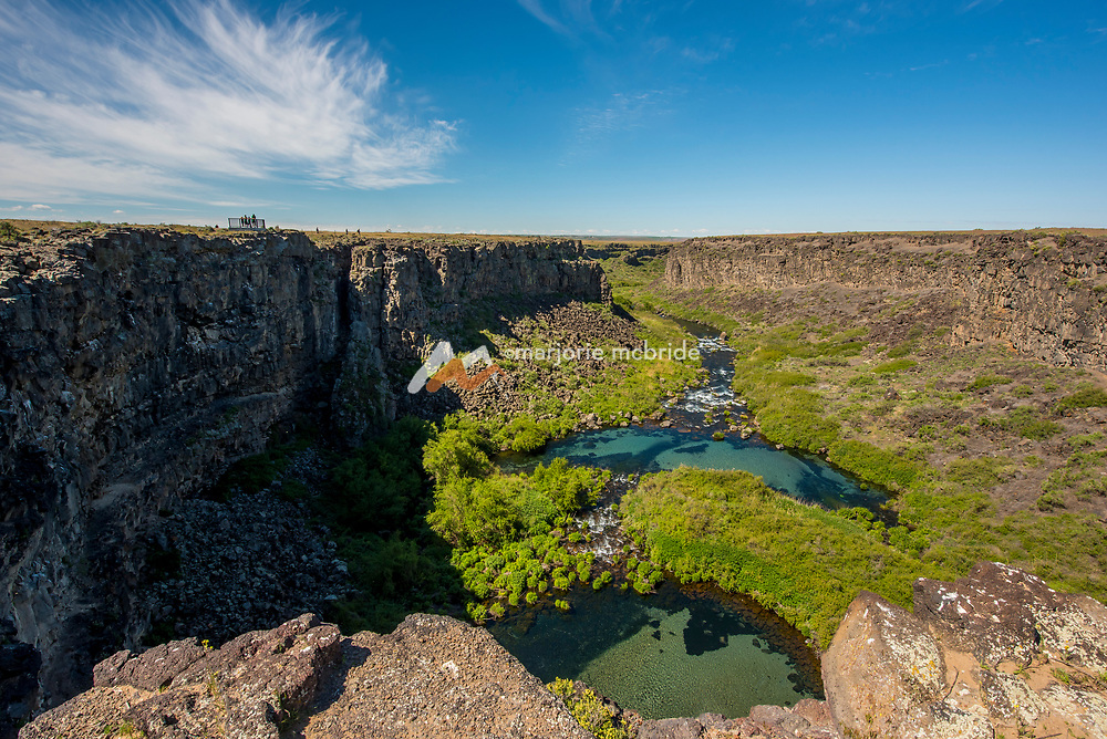 People in distance enjoying scenic view of plunge pools and crystal blue water at Box Canyon State Park in Wendell, Idaho.